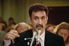 """Frank Zappa durante l'audizione del P.M.R.C.: """"All'obiezione che l'industria cinematografica è già sottoposta a un sistema di valutazione, Zappa risponde mostrando le differenze macroscopiche fra la produzione di un film e quella di un disco o di uno spettacolo musicale, specialmente per quanto riguarda l'esposizione individuale di ogni singolo collaboratore."""""""