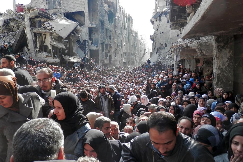 Gennaio 2015, rifugiati siriani in attesa di ricevere razioni di cibo nel campo profughi di Yarmouk, Siria